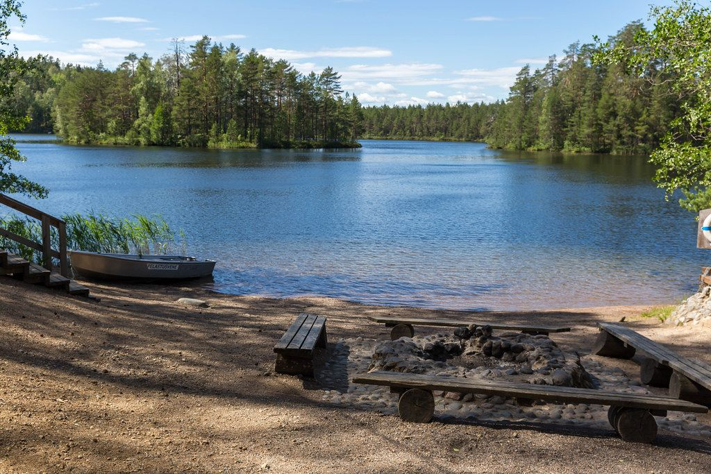 Fireplace made of stones with simple wooden benches on the island Kelvenne, at Lake Päijänne in Finland, next to a rowing boat