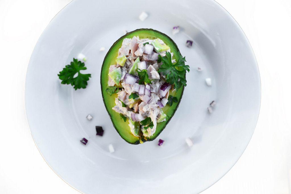 Fischsalat in einer halben Avocado mit roten Zwiebeln auf einem Teller in der Aufsicht
