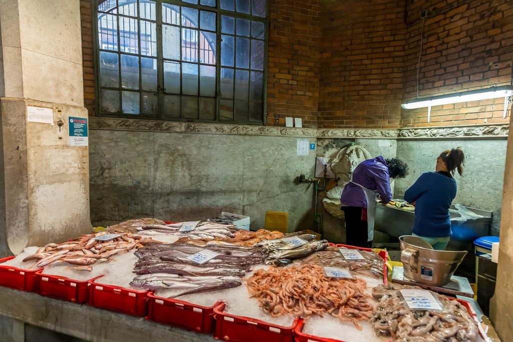Fish salesmen working behind counter full with fish in Rijeka, Croatia