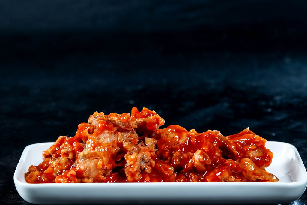 Fish stew in tomato sauce on black background