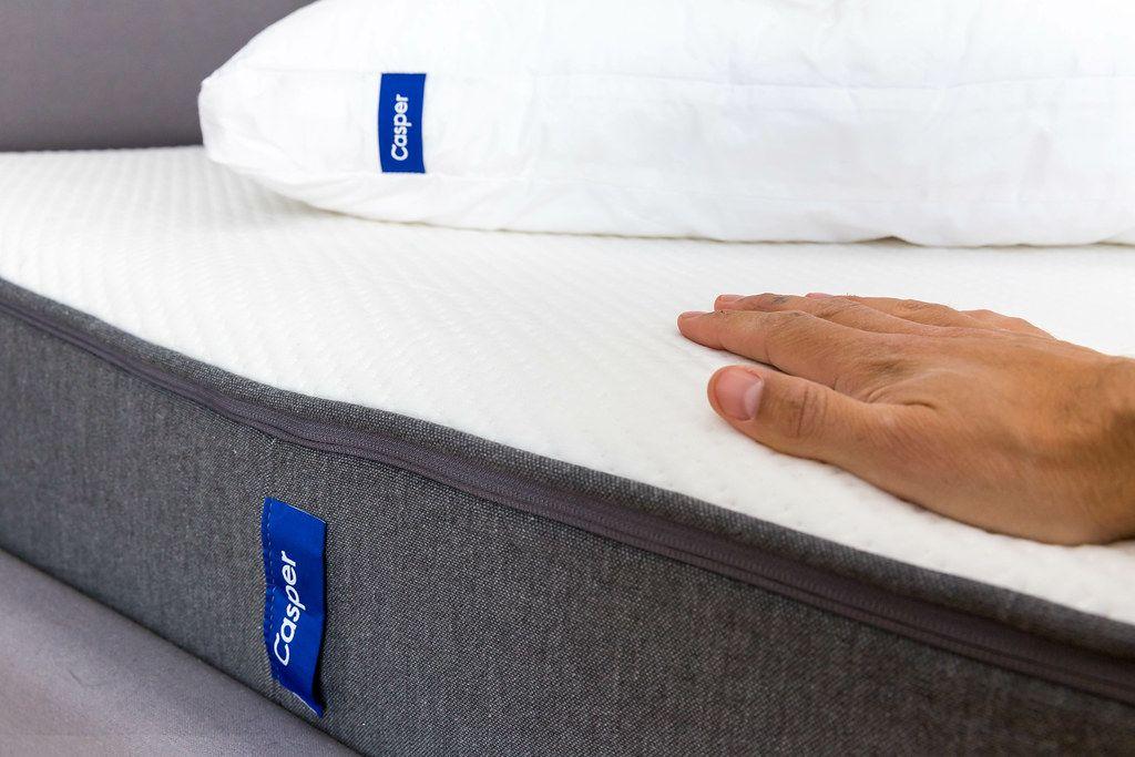 Flache Hand liegt auf der atmungsaktiven Matratze von Casper, die durch Memoryschaum den Körper im Schlaf entlastet