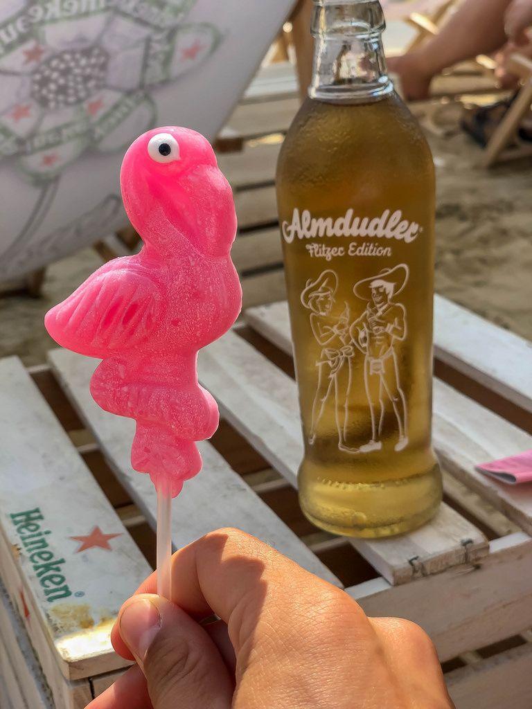 Flamingo Lutscher in der Hand und eine Flasche Almdudler Flitzer Edition im Hintergrund