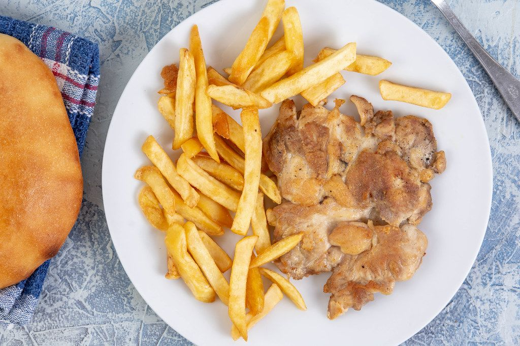 Flat lay above Chicken Drumstic with French Fries and bread