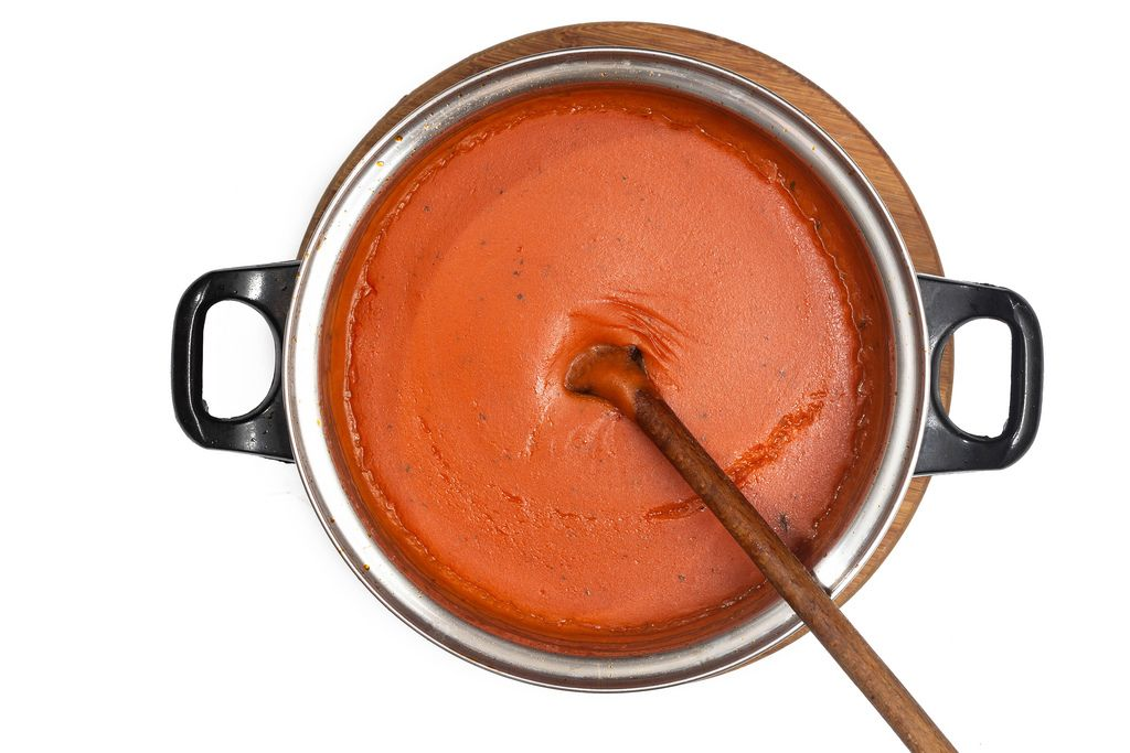Flat lay above fresh domestic homemade tomato sauce isolated over white background