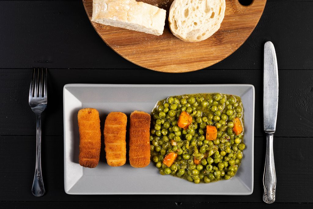 Flat lay above Fried Chicken Sticks with cooked Peas