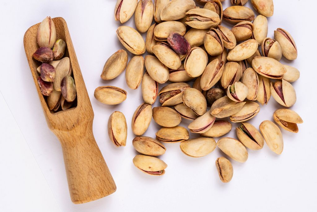 Flat lay above Pistachios with wooden Spatula