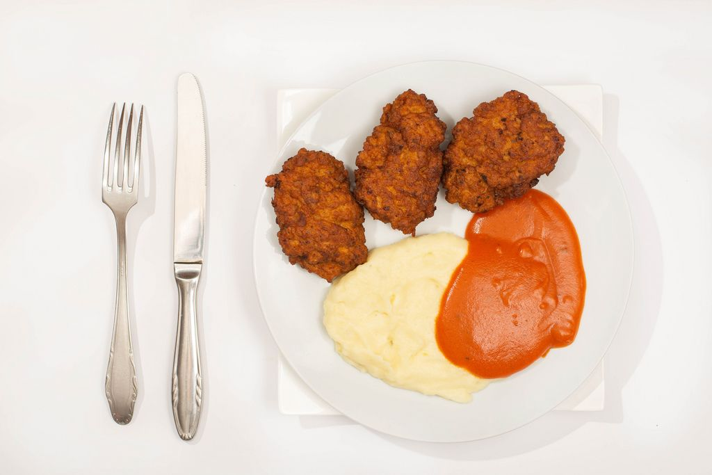 Flat lay above served meatballs with mashed potatoes and tomato sauce