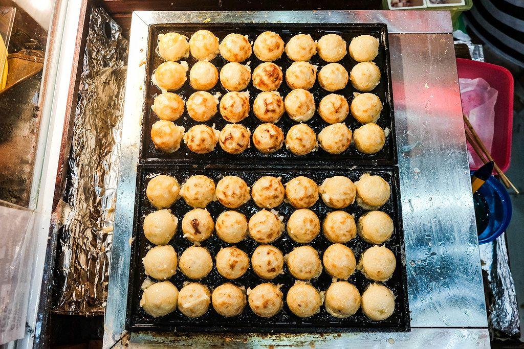 Flat lay of takoyaki balls on food tray