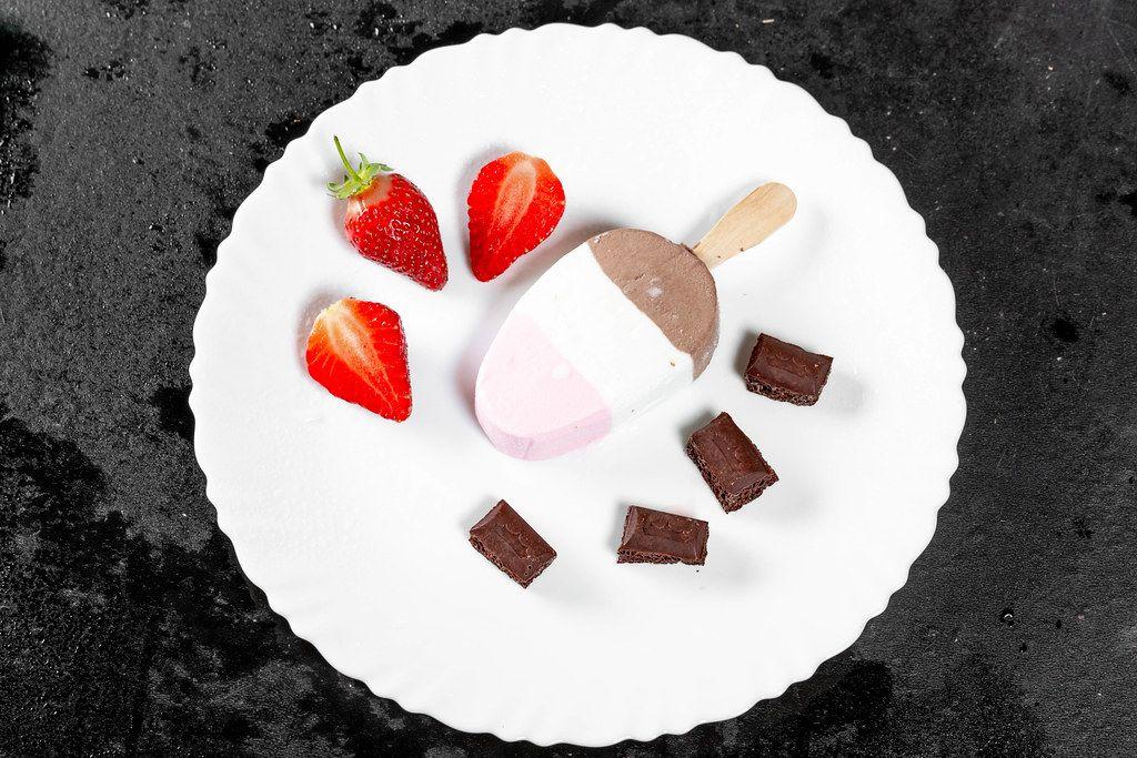Flatlay von dreifarbigen Eis mit Schokoladenwürfeln und frischen Erdbeeren auf weißem Teller