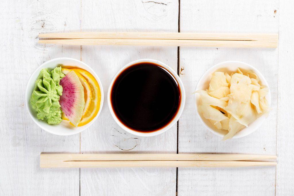 Flatlay von traditionellen Soßen für Sushi: Wasabi mit Zitrone, Sojasoße und Ingwer in weißen Schalen mit Essstabchen auf einem Holztisch