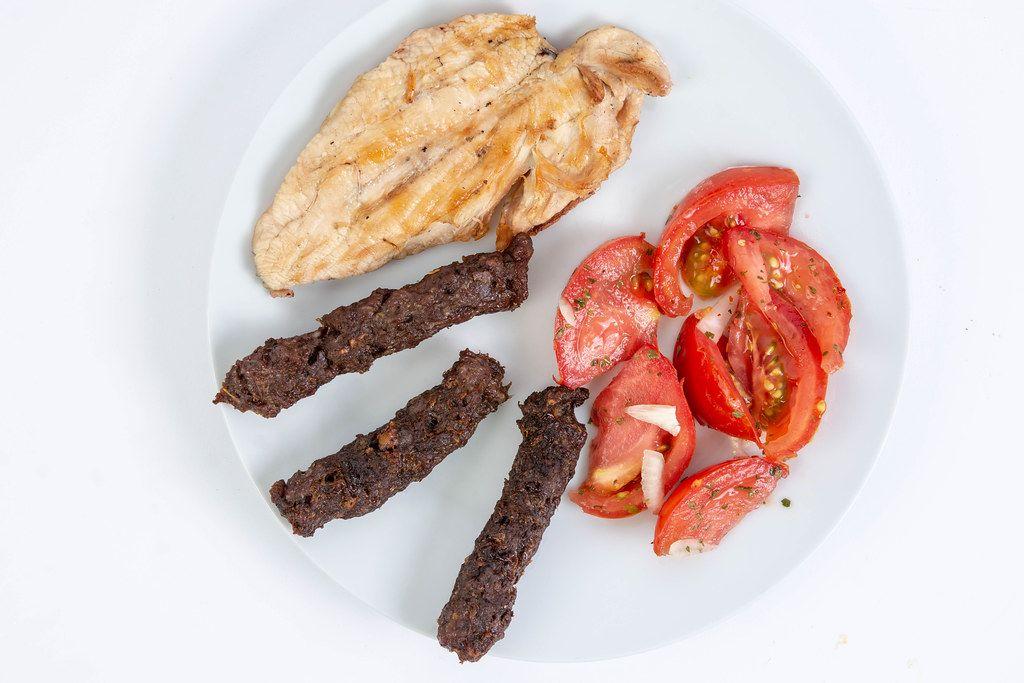 Flatlay zeigt Hühnchenbrust und Kebabs mit gewürzten Tomaten