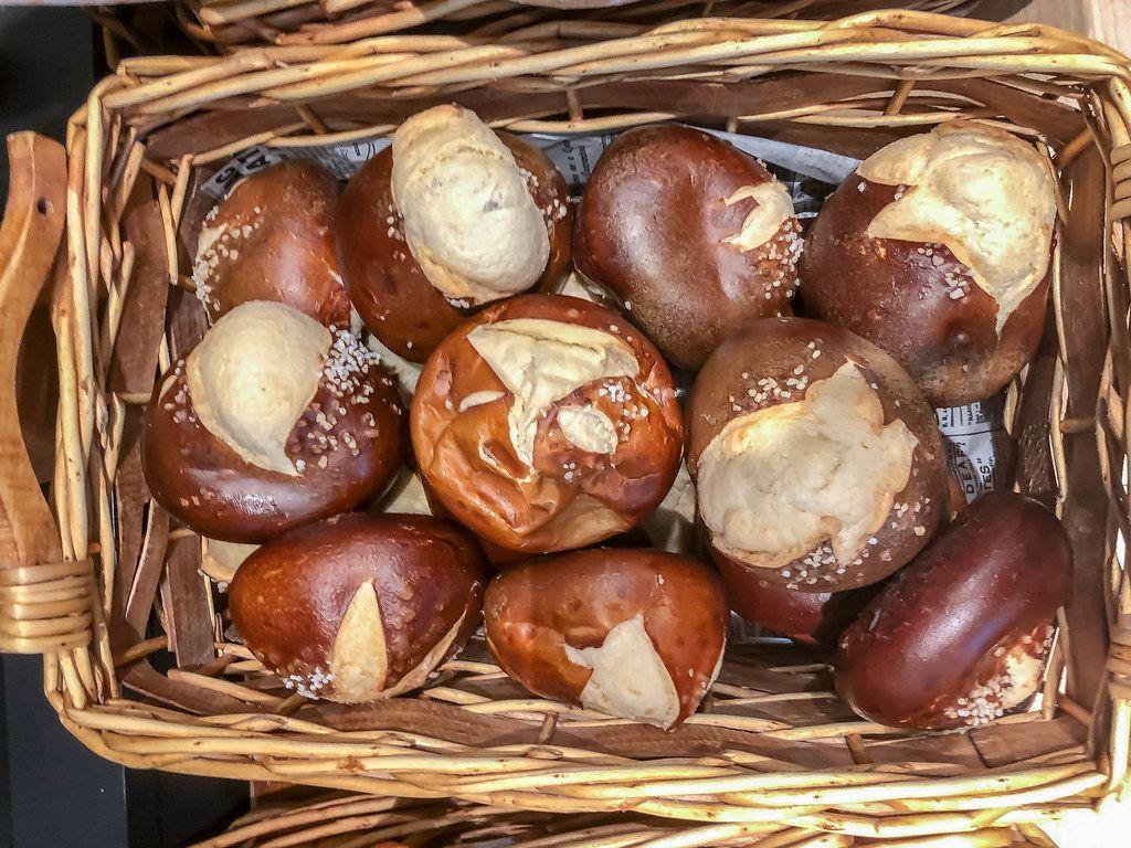 Flatlay zeigt Laugengebäck-Brötchen mit Salz bestreut, in einem Holzkorb