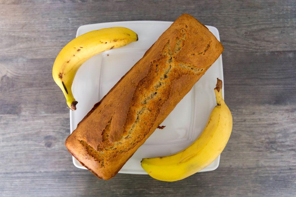 Flatlay zeigt selbstgebackenes Bananenbrot-Gebäck mit brauner Kruste, auf einem weißen Teller, auf einem Holztisch