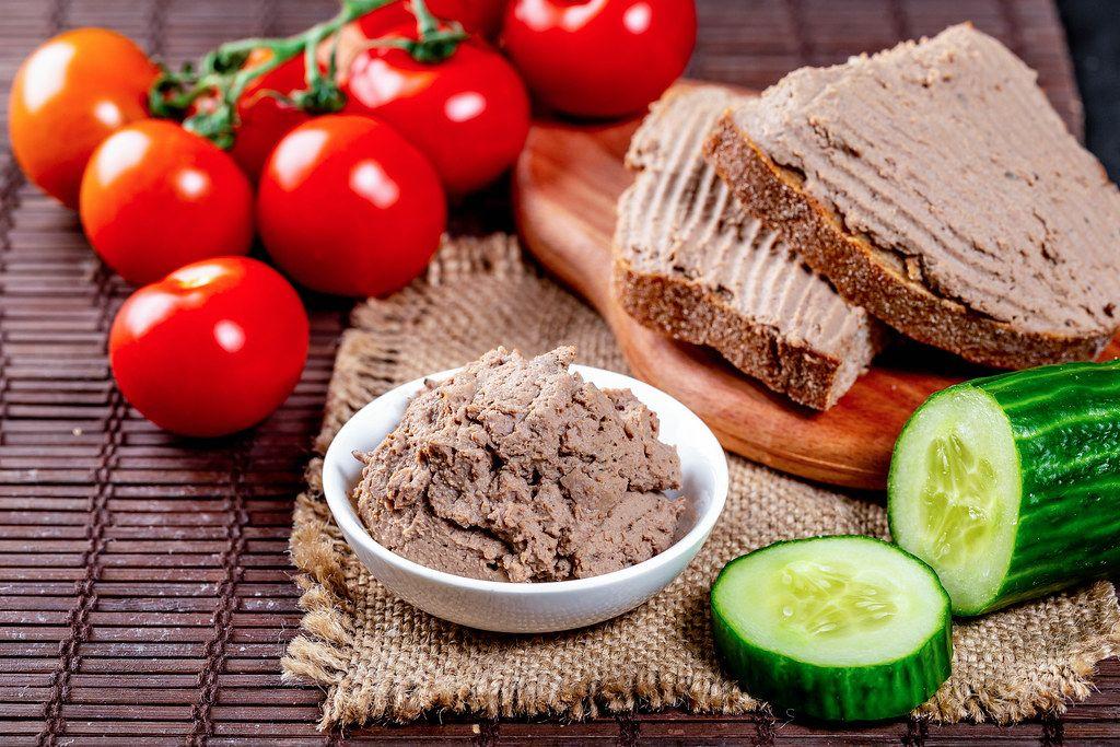 Fleischpastete in einer Schale als Brotaufstrich, neben Gurken und Tomaten, auf einer Leinendecke