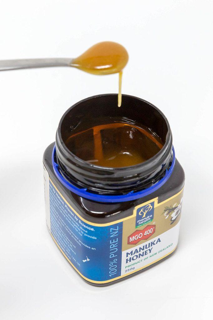 Flüssiger Honig tropft von einem Löffel ins Honigglas von Manuka Honey