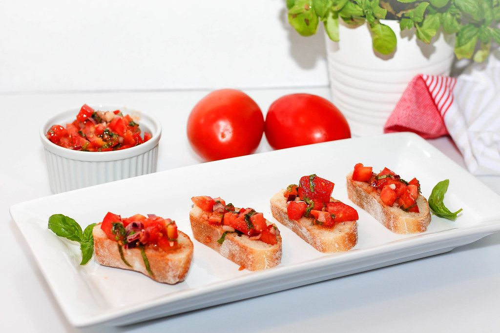 Food Photo of Tomato Bruschetta with Basil on a White Plate