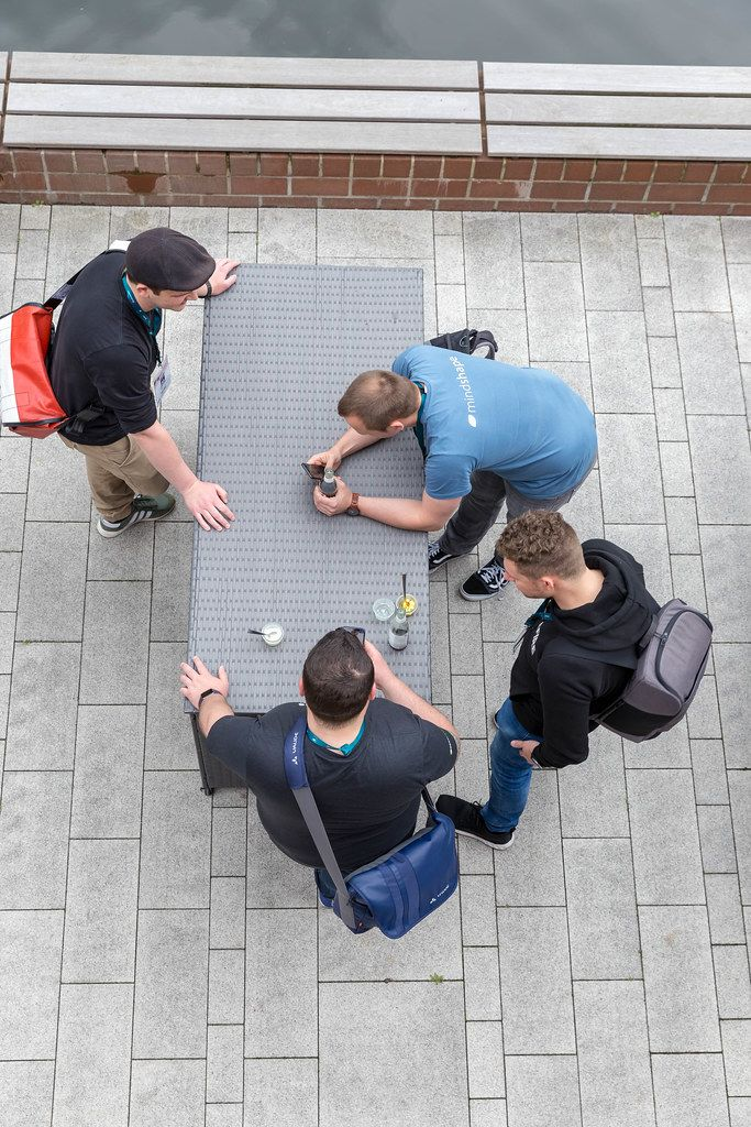 Four young men standing around a rattan table with smartphones and drinks on a terrace of the AXA-building at the Barcamp OMWest19 in Cologne.