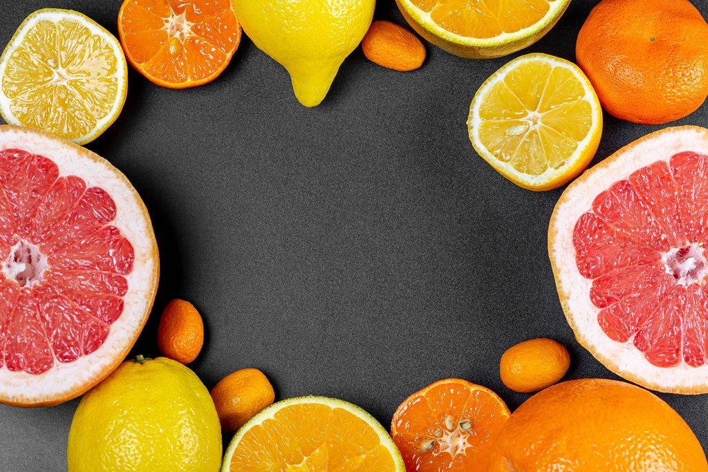 Frame of different citrus fruits on a black background with a free space in the middle