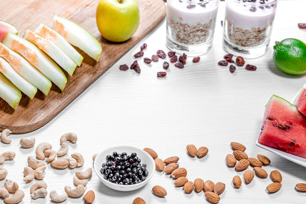 Frame of fruits, oatmeal and nuts for a healthy breakfast on a white wooden background