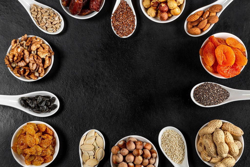 Frame of nuts, dried fruits and seeds on a black background with free space