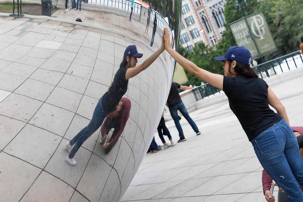 Frau berührt die Skulptur Cloud Gate