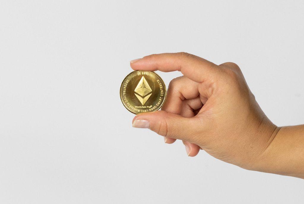 Frau hält eine Ethereum Münze