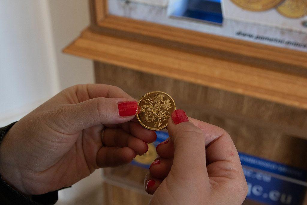 Frau hält eine goldene Münze in den Händen, die sie als Souvenir im Schloss Slavkov in Austerlitz gekauft hat