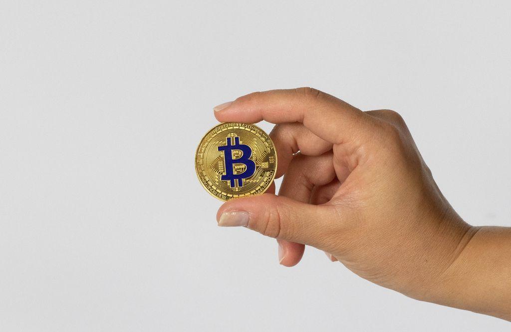 Frau hält einen goldenen Bitcoin