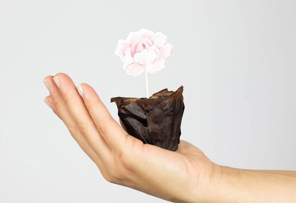 Frau hält einen Muffin mit Blumendekor in der Hand
