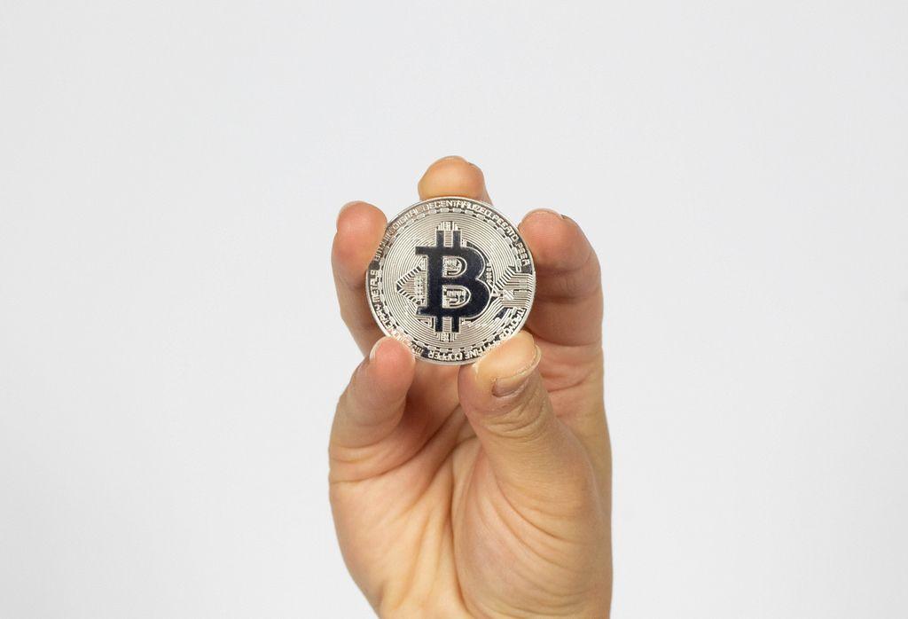 Frau hält einen silbernen Bitcoin in der Hand