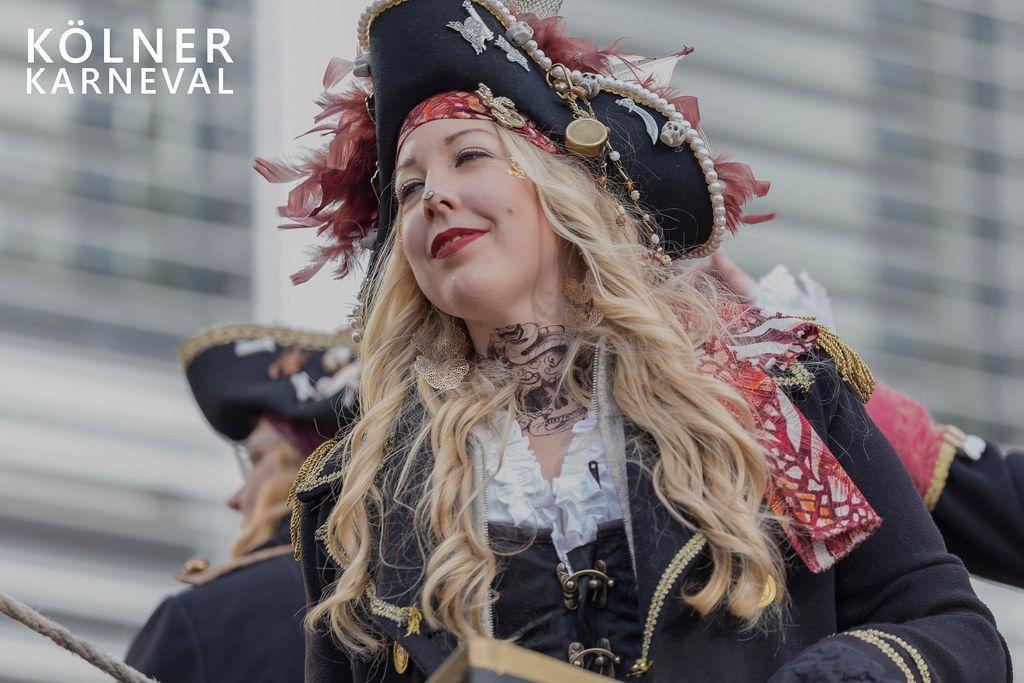 Frau im Kostüm als Piratenbraut verkleidet, fährt auf einem Festwagen beim Rosenmontagsumzug mit, neben dem Bildtitel
