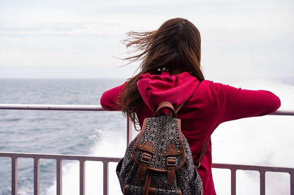 Frau im roten Pullover und Rücksack mit Blick aufs Meer
