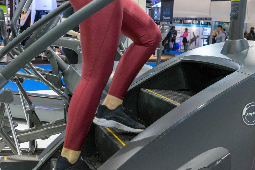 Frau in rotem Leggings träniert auf einer Anyfit Schrittmaschine an der Fibo-Messe Köln