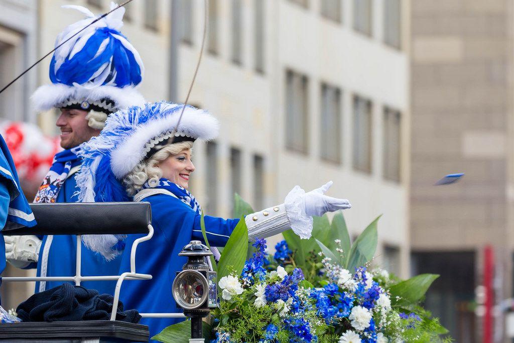 Frau in Uniform der Blauen Funken wirft Zuschauern Päckchen zu - Kölner Karneval 2018