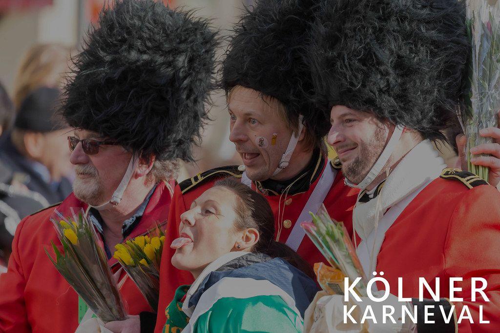 Frau macht ein Foto mit drei Gardisten während des Kölner Karneval