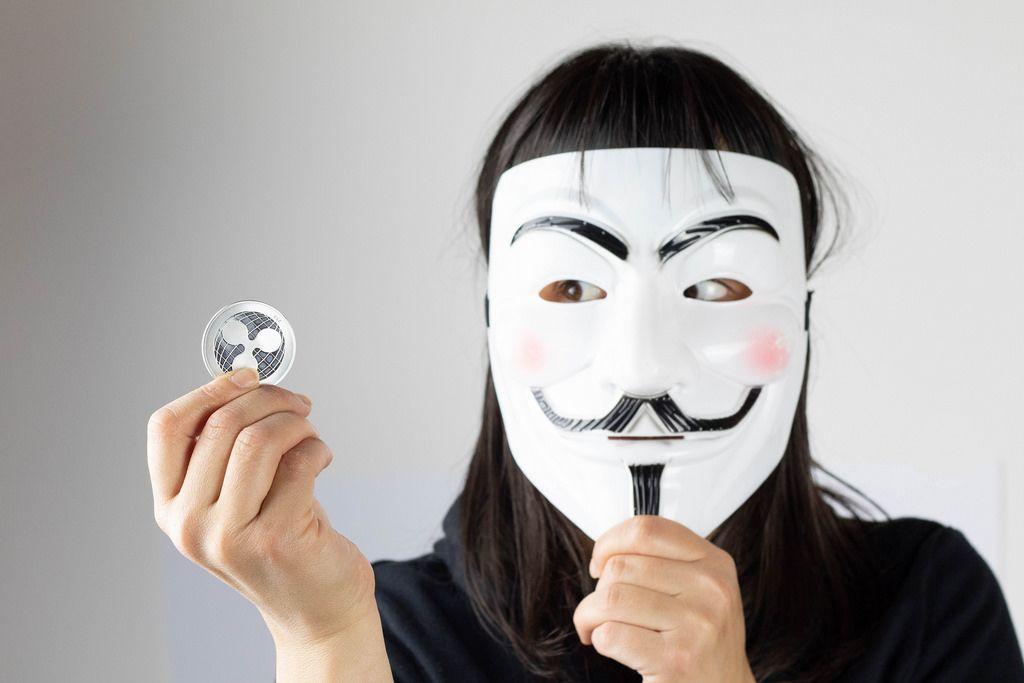Frau mit Guy Fawkes Maske hält Ripple Münze in der Hand