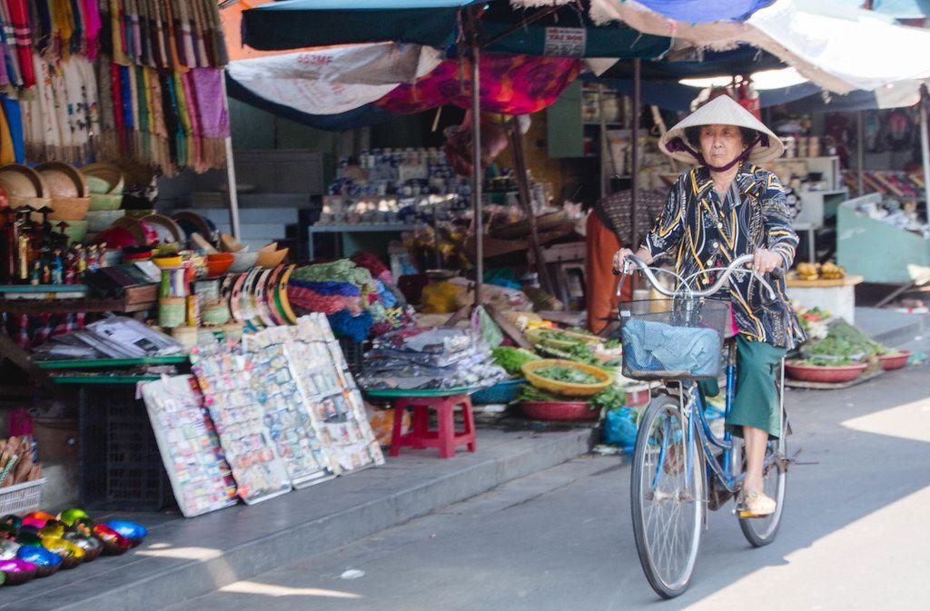 Frau mit Kegelhut auf einem Vintage-Fahrrad auf einem Marktplatz in Vietnam