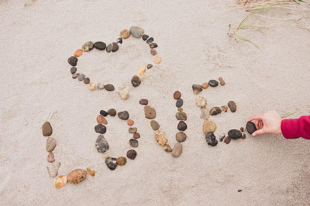 Frau schreibt mit Kiesen das Wort 'Liebe' mit einem Herzchen in den Sand