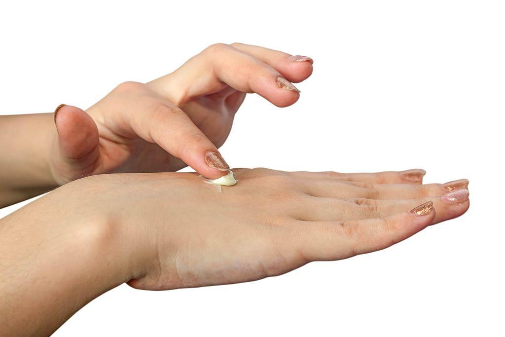Frau trägt Handcreme auf Handrücken auf vor weißem Hintergrund