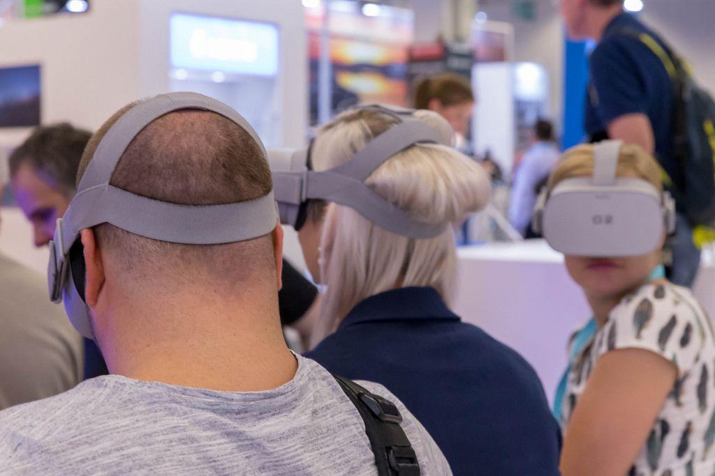 Frauen und ein Mann mit VR Brille an einem Messestand an der Photokina in Köln