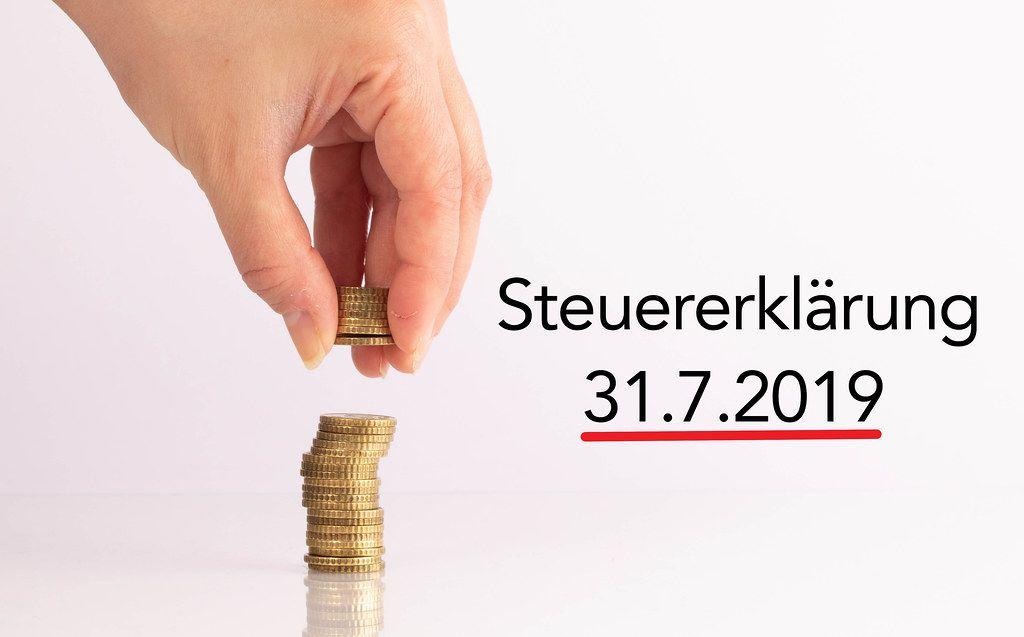 Frauenhand hebt Münzen auf mit dem Datum der Steuererklärung 2019