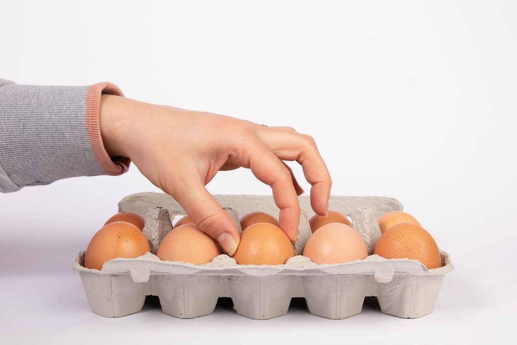Frauenhand nimmt braunes Hühnerei aus gefülltem Eierkarton von weißem Hintergrund