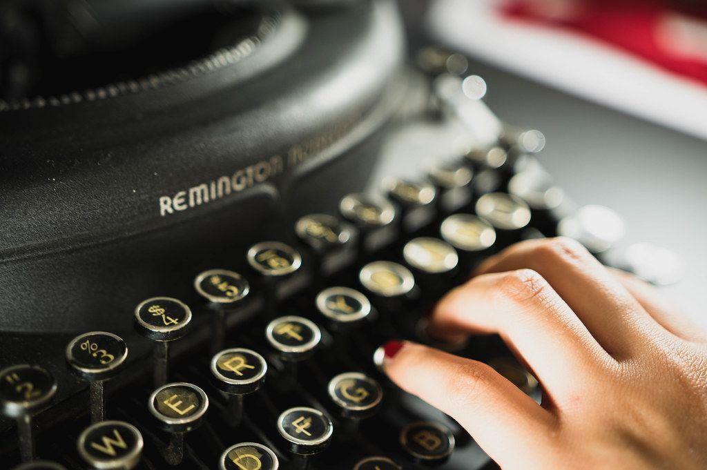 Frauenhand tippt auf einer alten Knopf-Tastatur