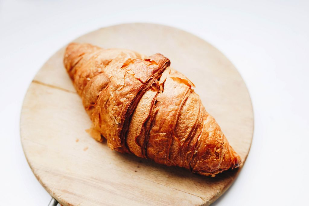 French croissant on wooden board. Close up.