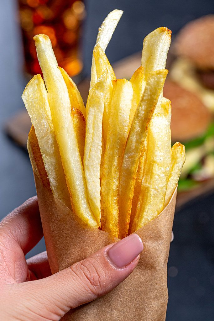 French fries in a paper wrapper in a woman's hand close up