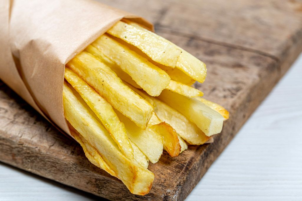 French fries in a paper wrapper on wooden board