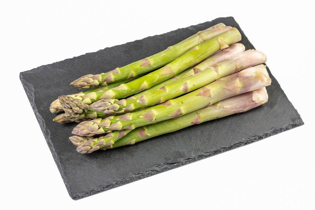 Fresh Asparagus on the black stone tray