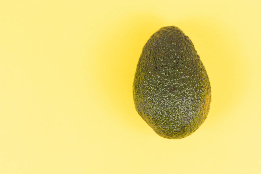 Fresh Avocado above yellow background with copy space