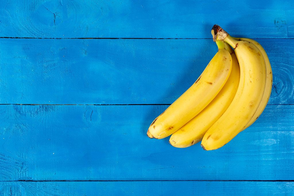 Fresh Bananas on the blue wooden table with copy space