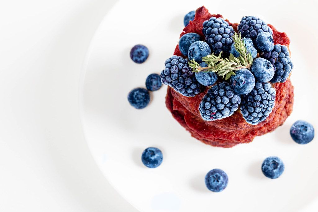 Fresh blueberry and mulberry berries on beet pancakes, top view